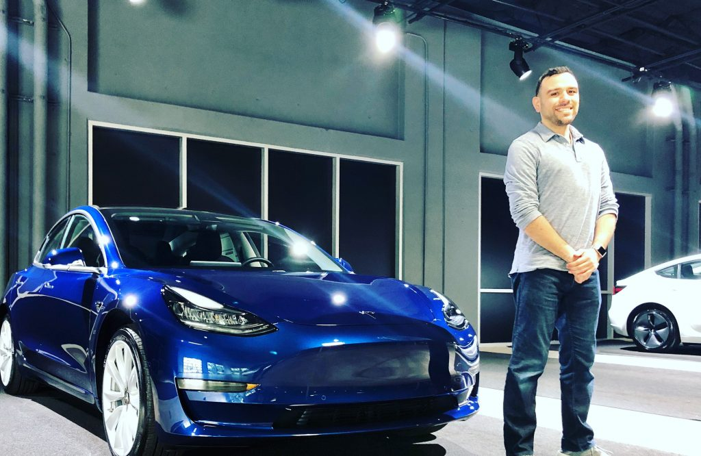 Héctor Ramos standing in front of a Tesla Model 3 at the Fremont Tesla Delivery Center.